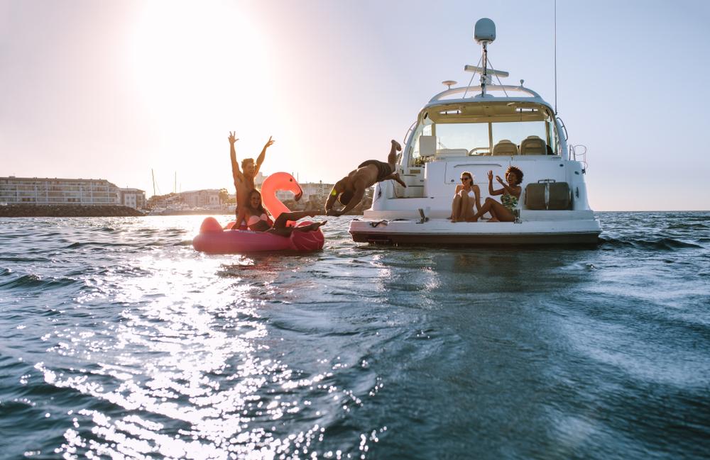 friends swimming near their yacht