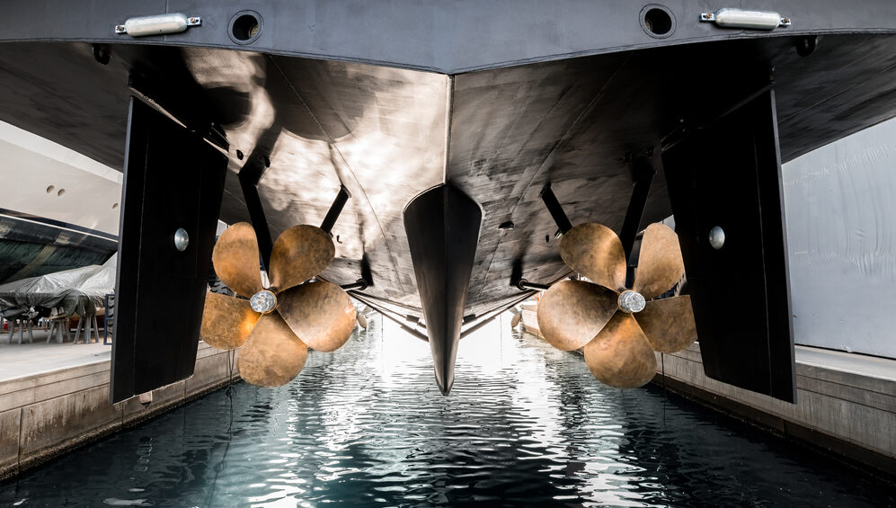 a yacht under maintenance is lowered into the water