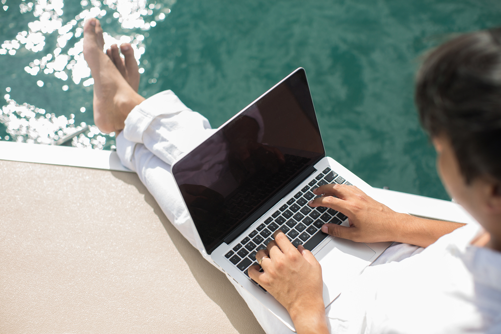 man typing on a laptop while on a yacht