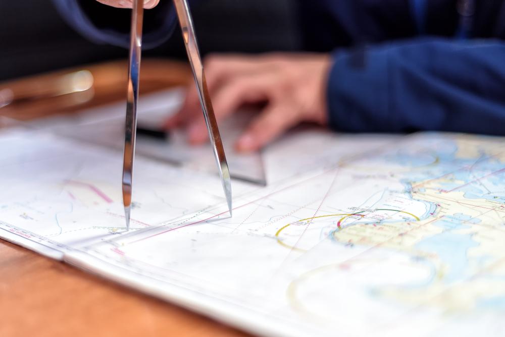 a captain checks his maps and charts before sailing