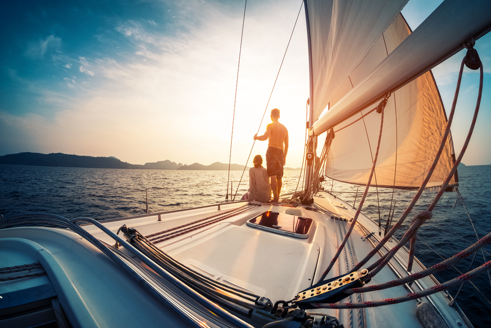 a couple sailing into the sunset on a yacht